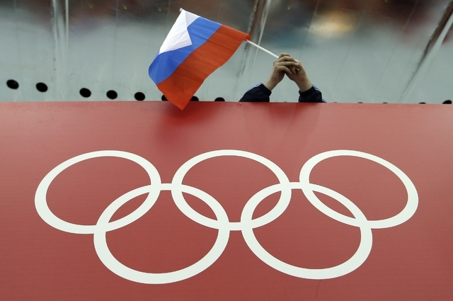 In this Feb. 18, 2014 file photo, a Russian skating fan holds the country's national flag over the Olympic rings before the start of the men's 10,000-meter speedskating race at Adler Arena Skating ...
