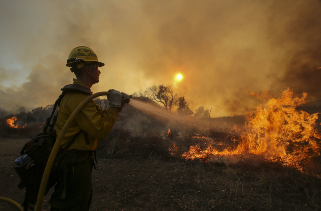 A firefighter battles a wildfire near Placenta Canyon Road in Santa Clarita, Calif., Sunday, July 24, 2016. Thousands of homes remained evacuated Sunday as two massive wildfires raged in tinder-dr ...