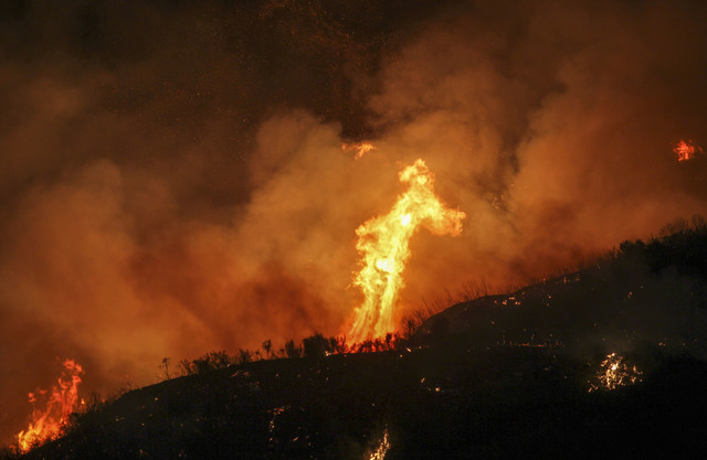 Flames flare up from a wildfire near Placenta Caynon Road in Santa Clarita, Calif., Sunday, July 24, 2016. Thousands of homes remained evacuated Sunday as two massive wildfires raged in tinder-dry ...