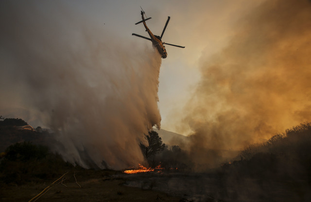 A helicopter maks a drop on a wildfire near Placenta Caynon Road in Santa Clarita, Calif., Sunday, July 24, 2016. Thousands of homes remained evacuated Sunday as two massive wildfires raged in tin ...