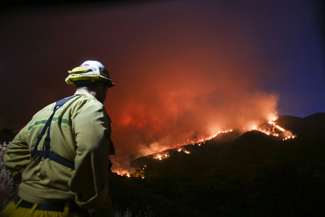 A firefighter watches a wildfire near Placenta Canyon Road in Santa Clarita, Calif., Sunday, July 24, 2016. Thousands of homes remained evacuated Sunday as two massive wildfires raged in tinder-dr ...