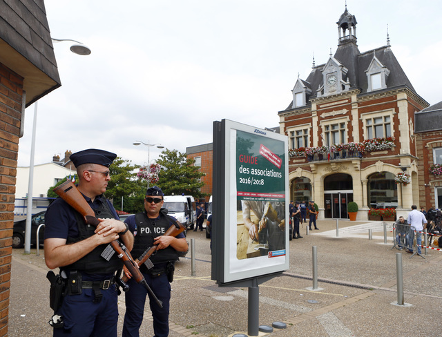 French police officers stand guard in front of the Saint-Etienne-du-Rouvray's city hall, Normandy, France, after an attack on a church that left a priest dead, Tuesday, July 26, 2016. (Francois Mo ...