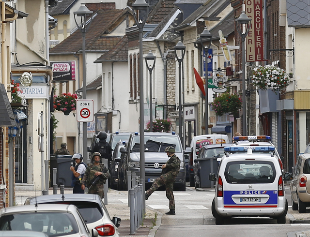 French soldiers stand guard near the scene of an attack in Saint-Etienne-du-Rouvray, Normandy, France, Tuesday, July 26, 2016. Two attackers invaded a church Tuesday during morning Mass near the N ...