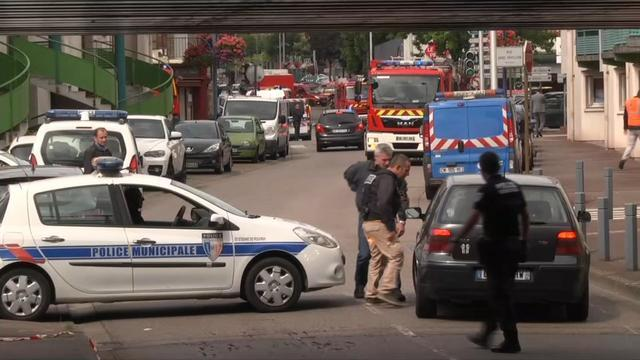 In this screen grab made from video, police officers speak to a driver as they close off a road during a hostage situation in Normandy, France, Tuesday, July 26, 2016. Two attackers seized hostage ...
