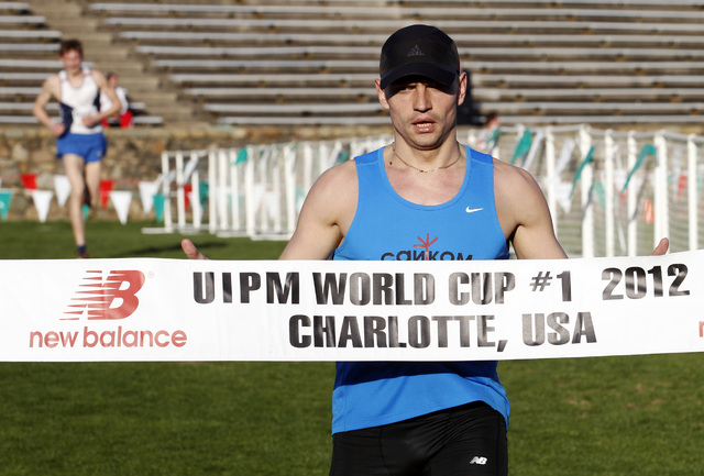 In this Sunday, March 11, 2012 file photo, Russia's Ilia Frolov runs through the finish line tape as he wins the men's final in the Modern Pentathlon World Cup in Charlotte, in the U.S. Two Russia ...