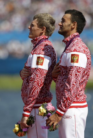 In this Saturday, Aug. 11, 2012 file photo Russia's Yury Postrigay, left, and Alexander Dyachenko listen to the national anthem on the podium after winning the gold medal in the men's kayak double ...