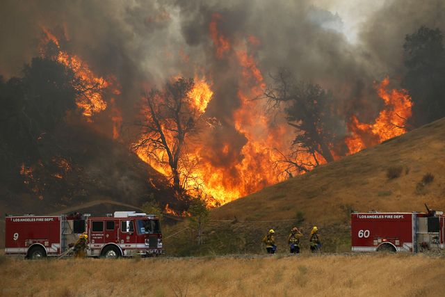 A hillside erupts in flame as a wildfire burns in Placerita Canyon in Santa Clarita, Calif., Monday, July 25, 2016. (Nick Ut/AP)