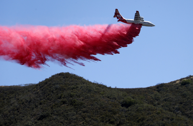 A plane drops fire retardant on an unburned ridge in advance of flames as a wildfire fire burns in Placerita Canyon in Santa Clarita, Calif., Monday, July 25, 2016. (Nick Ut/AP)