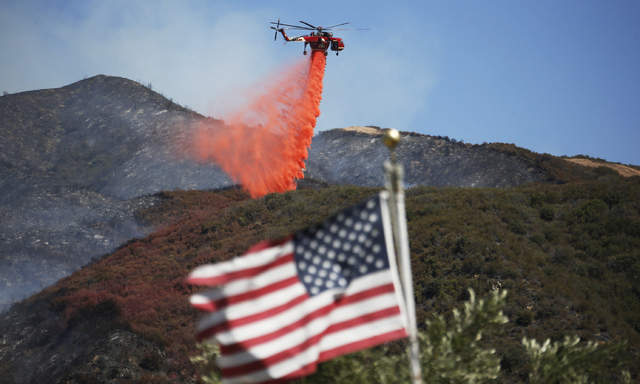 Framed by a burned-over hillside, rear, and an American flag in the foreground, a helicopter drops fire retardant ahead of advancing flames as a wildfire approaches Placerita Canyon in Santa Clari ...