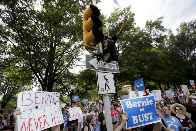 A supporter of Sen. Bernie Sanders, I-Vt., yells at delegates over fence after climbing a light pole in Franklin Delano Roosevelt Park in Philadelphia, Tuesday, July 26, 2016, during the second da ...