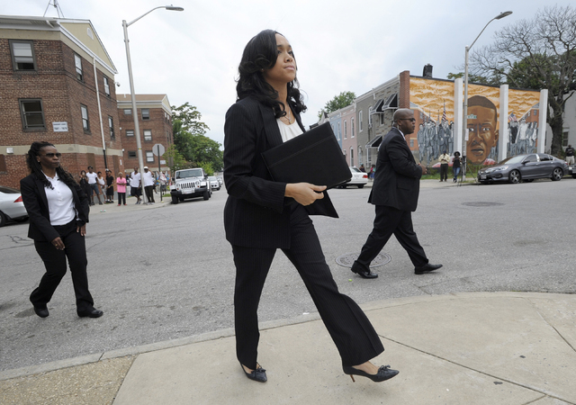 Baltimore State's Attorney Marilyn Mosby, center, arrives for a news conference near the site where Freddie Gray, depicted in the mural at right, was arrested, after her office dropped the remaini ...