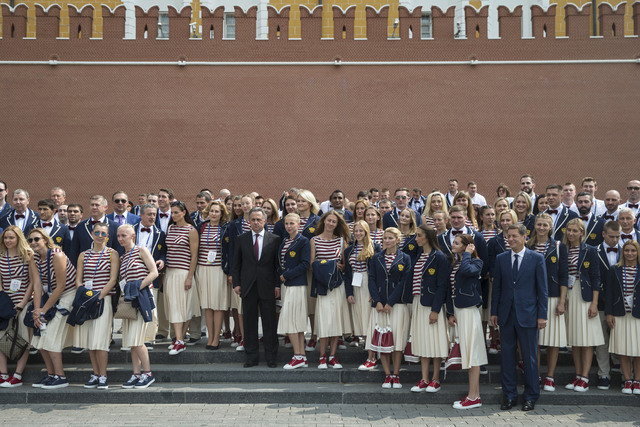 President of Russia's Olympic Committee Alexander Zhukov, fourth right, and Sports Minister Vitaly Mutko, center, pose for a photo with Russia's National Olympic team members outside the Kremlin w ...