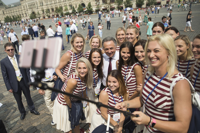 Russia's Sports Minister Vitaly Mutko with members of the Russia's National Olympic team members a one takes a take a selfie as they walk for a meeting with Russian President Vladimir Putin, in Mo ...