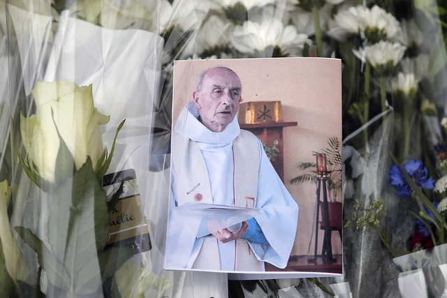 A picture of the late Rev. Jacques Hamel is placed on flowers at the makeshift memorial in front of the city hall close to the church where a hostage taking left the priest dead this week in Saint ...