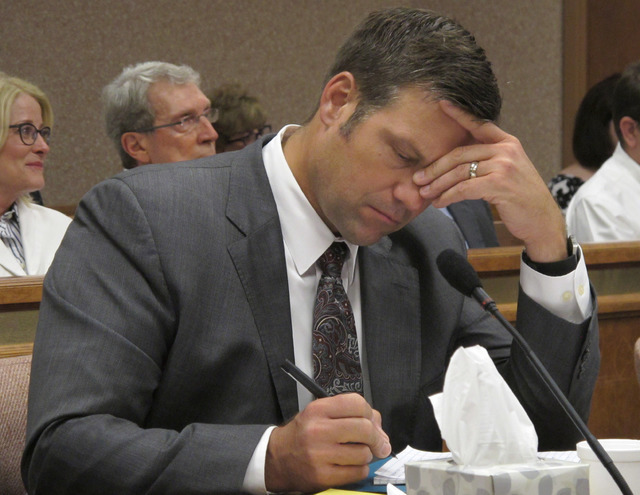 Kansas Secretary of State Kris Kobach listens and takes note as a judge declares in Shawnee County District Court that the state must count potentially thousands of votes from people who registere ...
