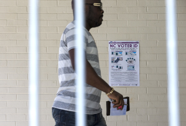 This March 15, 2016, file photo shows Eric Gandah walking past a NC Voter ID sign as he enters a precinct to cast his ballot in Greensboro, N.C. (H. Scott Hoffmann/News & Record via AP, File)