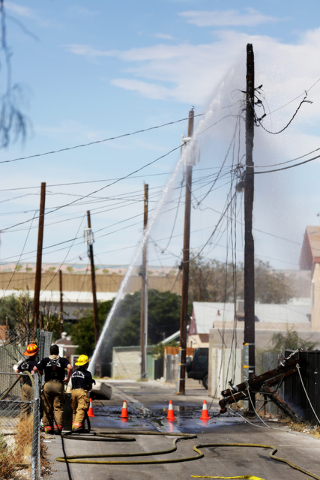 Firefighters extinguish the remains of a telephone pole after responding to a house fire at 309 N. Eighth St. near Las Vegas Boulevard Saturday, July 16, 2016, in Las Vegas. Rachel Aston/Las Vegas ...