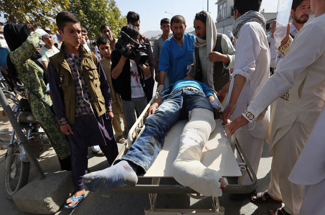 Afghans help an injured man at a hospital after an explosion struck a protest march, in Kabul, Afghanistan, Saturday, July 23, 2016. (Rahmat Gul/The Associated Press)