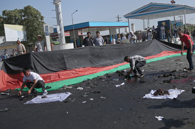 Afghans gather property, left behind by victims of a deadly explosion that struck a protest march by ethnic Hazaras, in Kabul, Afghanistan, Saturday, July 23, 2016. (Massoud Hossaini/The Associate ...