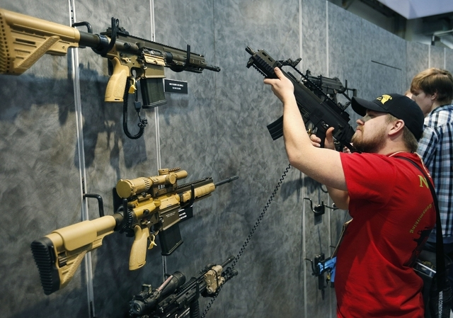 Nolan Hammer looks at a gun at the Heckler & Koch booth at the Shooting, Hunting and Outdoor Trade Show in Las Vegas in January. (John Locher/The Associated Press)
