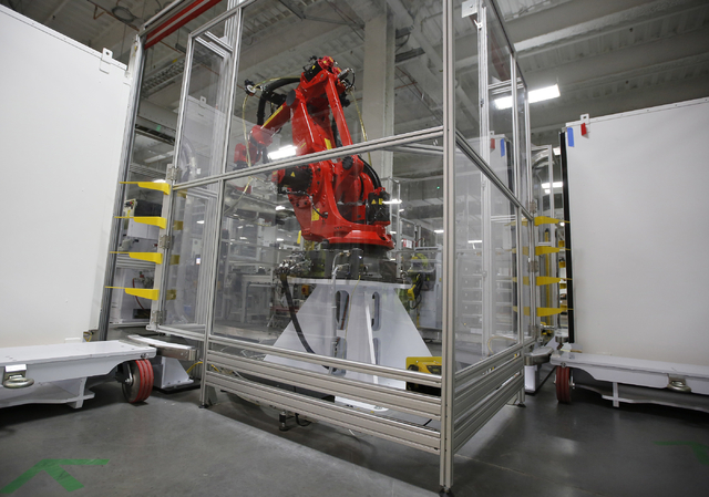 A robot used at the new Tesla Motors Inc., Gigafactory is displayed Tuesday, July 26, 2016, in Sparks, Nev. It's Tesla Motors biggest bet yet: a massive, $5 billion factory in the Nevada desert th ...