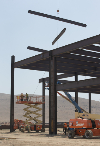 Support beams are lowered in to position during the construction of the new Tesla Motors Inc., Gigafactory, Tuesday, July 26, 2016, in Sparks, Nev. It's Tesla Motors biggest bet yet: a massive, $5 ...