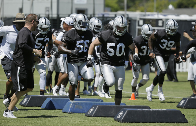 Oakland Raiders linebacker Ben Heeney (50) followed by Daren Bates (56) run through obstacles during practice at the NFL football team's training camp Friday, July 29, 2016, in Napa, Calif. (AP Ph ...