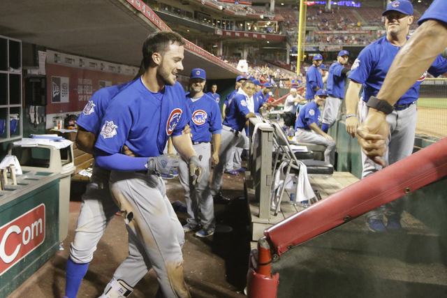 Chicago Cubs third baseman Kris Bryant, center left, resists encouragement to wave to the crowd at a baseball game, Monday, June 27, 2016, in Cincinnati. The Cubs won 11-8. (John Minchillo/Associa ...