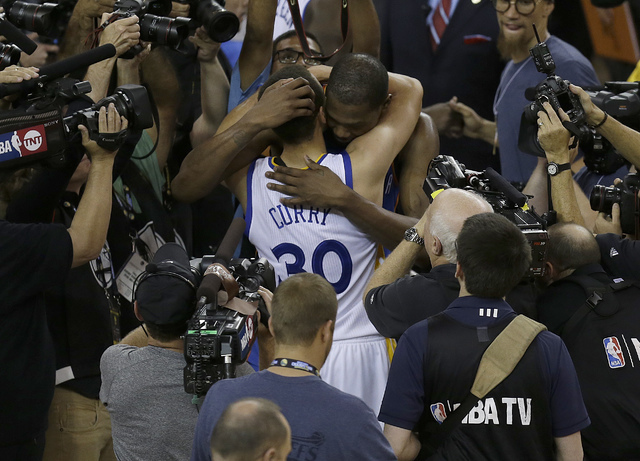 Golden State Warriors guard Stephen Curry (30) hugs Oklahoma City Thunder forward Kevin Durant after Game 7 of the NBA basketball Western Conference finals in Oakland, Calif., Monday, May 30, 2016 ...