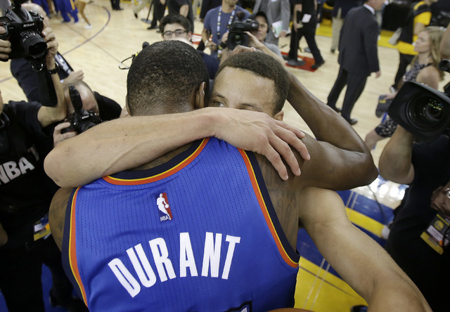 Oklahoma City Thunder forward Kevin Durant, foreground, hugs Golden State Warriors guard Stephen Curry after Game 7 of the NBA basketball Western Conference finals in Oakland, Calif., Monday, May  ...