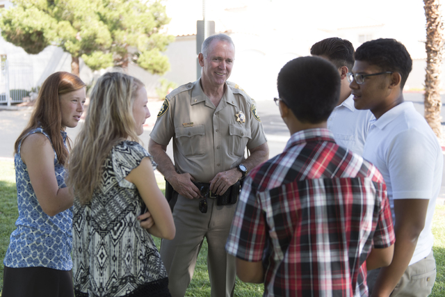 Las Vegas police Deputy Chief Jim Owens, center, speaks with a group of teenagers during an outreach event held at Torrey Pines Condominiums following Wednesday night's quadruple murder-suicide of ...