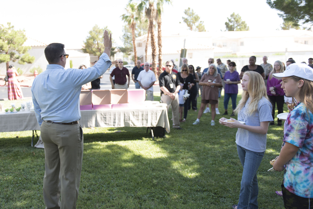 Pastor Matt Teis of Liberty Baptist Church, left, speaks to attendees during an outreach event held at Torrey Pines Condominiums following Wednesday night's quadruple murder-suicide of a family in ...