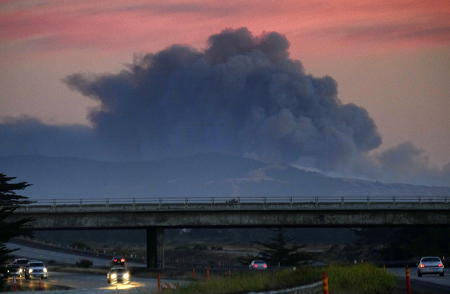 A large plume of smoke from a wildfire rises near Highway 1, burning five miles south of Carmel, Calif., on Friday, July 22, 2016. (Richard Vogel/The Associated Press)
