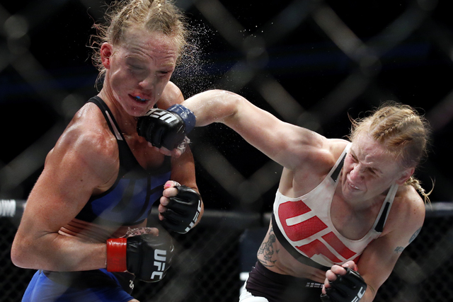 Valentina Shevchenko, right, of Kyrgyzstan, punches Holly Holm during a women's bantamweight mixed martial arts bout in Chicago, Saturday, July 23, 2016. (Nam Y. Huh/Associated press)