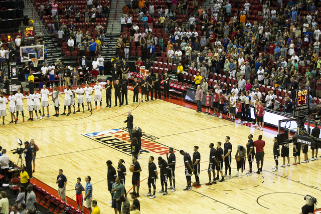 People including players from the Phoenix Suns and the Miami Heat sing the National Anthem before the start of their game during the NBA Summer League at the Thomas and Mack Center on Tuesday, Jul ...