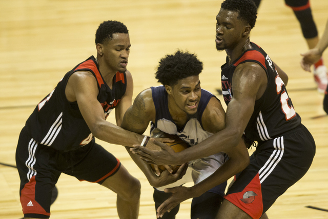 Utah Jazz Quincy Ford (17), center, holds control of the ball as he is fouled by Portland Trail Blazers Luis Montero (44), left, and Noah Vonleh (21) during a NBA Summer League game at the Thomas  ...