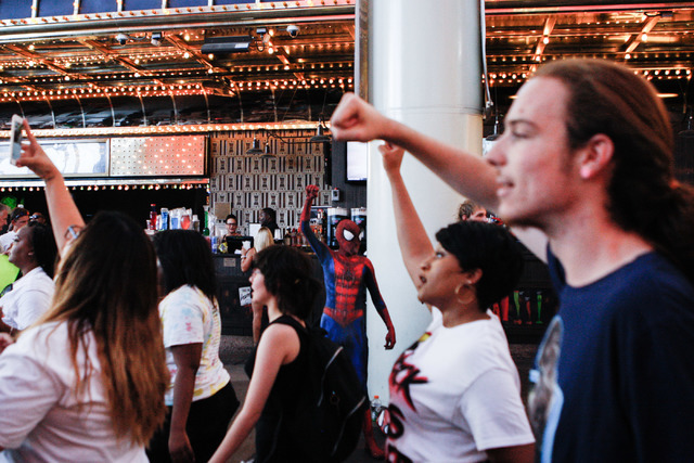 Protesters march in downtown Las Vegas during a Black Lives Matter demonstration while a bystander dressed as Spider Man joins putting a fist in the air Saturday evening, July 16, 2016.(Elizabeth  ...