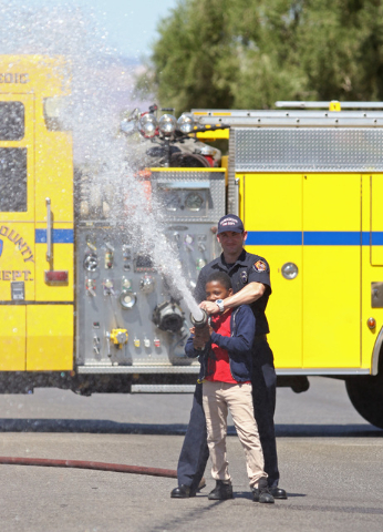 Clark County Fire Department firefighter Daniel Mawhinney assists Tyriq Beacham, 12, with opening a hose for children to play in water during a neighborhood block party on Viking Road near Wynn Ro ...
