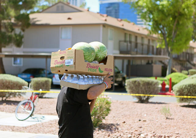 A man carries groceries he was given during a neighborhood block party on Viking Road near Wynn Road on Saturday, July 23, 2016, in Las Vegas. Metropolitan Police Department Enterprise Area Comman ...