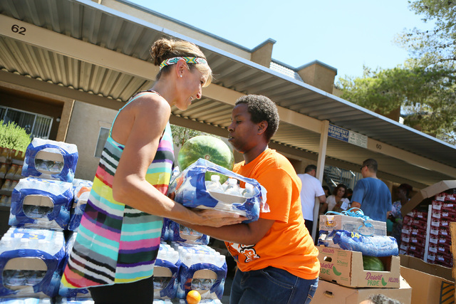 Jessica Nelson, left, hands a flat of water to Annette Wesley during a neighborhood block party on Viking Road near Wynn Road on Saturday, July 23, 2016, in Las Vegas. Metropolitan Police Departme ...