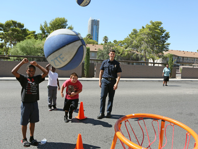 Clark County Fire Department firefighter Frank Consiglio, right, plays basketball with children during a neighborhood block party on Viking Road near Wynn Road on Saturday, July 23, 2016, in Las V ...