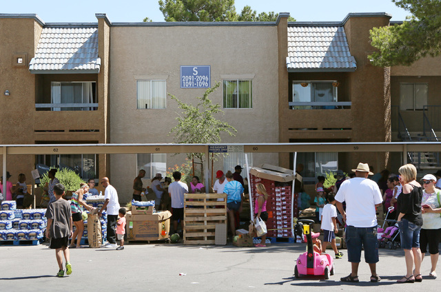 People browse a free food pantry during a neighborhood block party on Viking Road near Wynn Road on Saturday, July 23, 2016, in Las Vegas. Metropolitan Police Department Enterprise Area Command ho ...