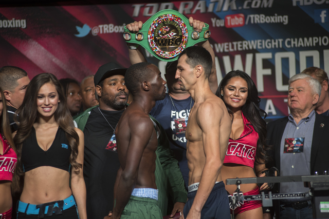 Boxers Terence Crawford, center in green pants, and Viktor Postol pose ahead of their Junior Welterweight title fight during the weigh-in event at the MGM Grand Garden Arena in Las Vegas on Friday ...