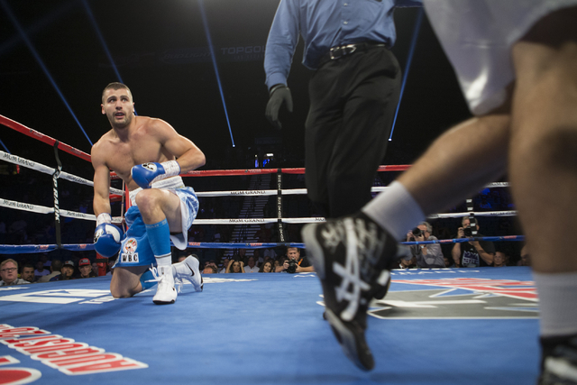 Oleksandr Gvozdyk takes a knee after getting punched by Tommy Karpency in the light heavyweight NABF Championship bout at the MGM Grand Garden Arena on Saturday, July 23, 2016, in Las Vegas. (Erik ...