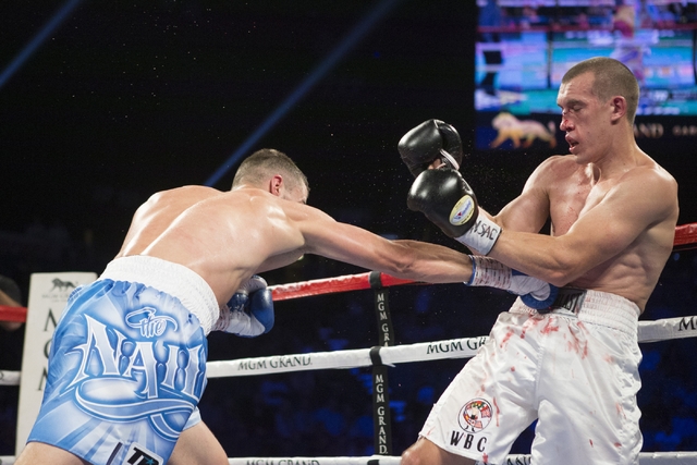 Oleksandr Gvozdyk, left, connects a right punch to force Tommy Karpency to take a knee and win by technical knockout in the sixth round of the light heavyweight NABF Championship bout at the MGM G ...