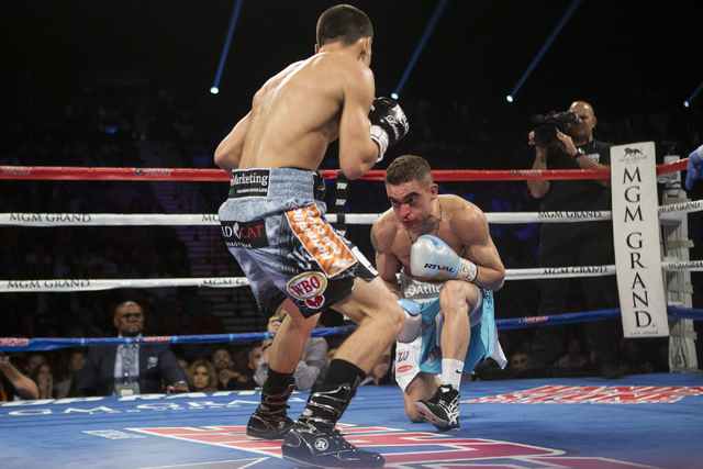 Matias Rueda, right, takes a knee against Oscar Valdez Jr. in the featherweight title bout for the vacant WBO World Title at the MGM Grand Garden Arena on Saturday, July 23, 2016, in Las Vegas.(Er ...