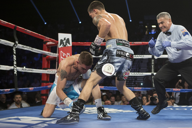 Oscar Valdez Jr., right, takes down Matias Rueda with a punch in the featherweight title bout for the vacant WBO World Title at the MGM Grand Garden Arena on Saturday, July 23, 2016, in Las Vegas. ...
