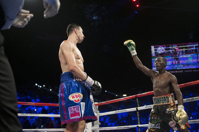 Terence Crawford, right, raises his arm in taunt against Viktor Postol in the WBO and WBC World Title bout at the MGM Grand Garden Arena on Saturday, July 23, 2016, in Las Vegas. (Erik Verduzco/La ...