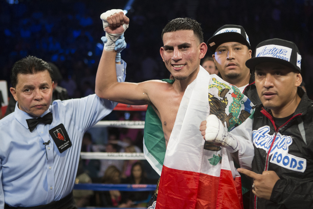 Jose Benavidez Jr., raises his arm in victory after his unanimous decision win against Francisco Santana in the welterweight bout at the MGM Grand Garden Arena on Saturday, July 23, 2016, in Las V ...