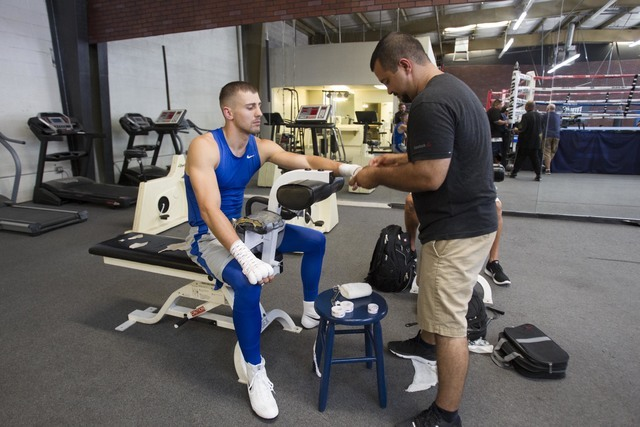 Ukrainian boxer Oleksandr Gvozdyk, left, gets his hands wrapped by Marco Contreras before training during media day workouts at the Top Rank boxing gym in Las Vegas on Tuesday, July 19, 2016. (Ric ...